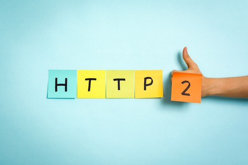 Website protocol HTTP:2 on blue background. Hand making thumb up gesture